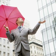 Young businessman balancing with red umbrella in city